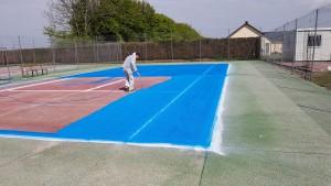 application de peinture sur le terrain de tennis