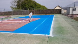 Application de peintures sur le terrain de tennis