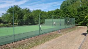 Application de peinture sur le mur d'entrainement et court de tennis